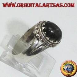 Серебряное кольцо с черной звездой окружено точками