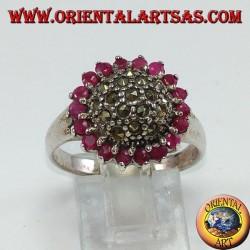 Anillo redondo de plata con un hemisferio de marcasita rodeado de 18 rubíes redondos.