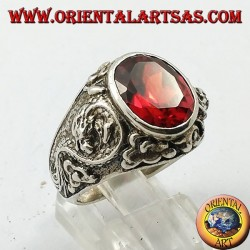 Silver ring with oval faceted garnet and stylized dragon in high relief on the sides