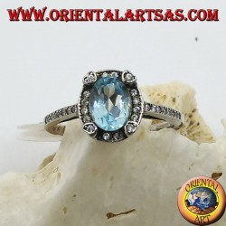 Silver ring with natural oval blue topaz set surrounded by zircons