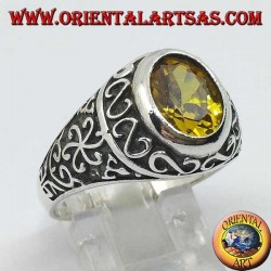 Silver ring with oval yellow topaz surrounded by S and floral decorations on the sides