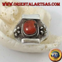 Silver ring with antique Tibetan oval coral and Nepalese setting with flower on the sides