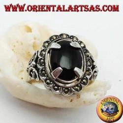 Bague en argent sertie d'un cabochon ovale en onyx et entourée de boules de marcassite