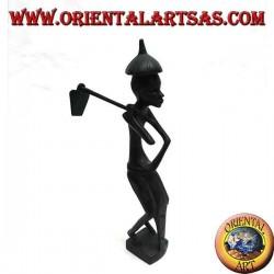 Skulptur eines Bauern, der eine Hacke auf der Schulter und einen spitzen Ebenholzhut hält