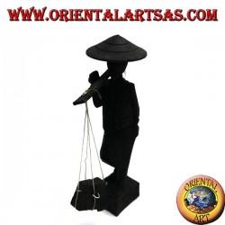 Sculpture d'un ancien coursier avec chapeau de paille et bâton avec des produits en bois d'ébène sur l'épaule