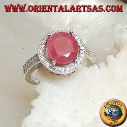 Silver ring with oval natural ruby set on a round frame with zircons