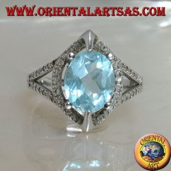 Silver ring with oval natural blue topaz set on shuttle frame with zircons