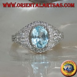 Silver ring with oval natural blue topaz on a zircon-studded frame and three rounds on the sides