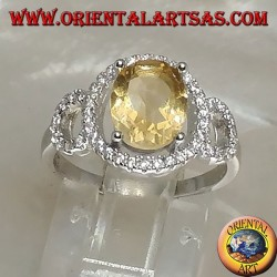Silver ring with oval natural yellow topaz set on a three circle of zirconia setting