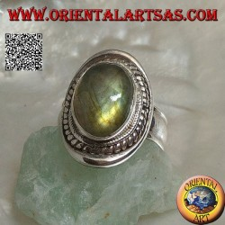 Silver ring with oval cabochon labradorite surrounded by intertwining on a smooth shield