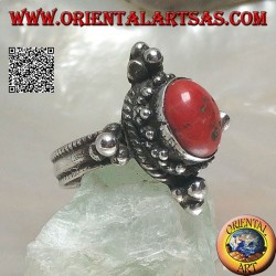 Silver ring with oval Tibetan antique coral surrounded by dots on a Nepalese setting