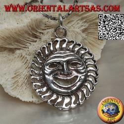 Colgante de plata en forma de sol con una cara satírica / irónica.