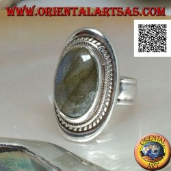 Silver ring with large oval labradorite in blue fluorescence cabochon surrounded by weaving on a smooth shield