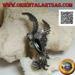 Silver brooch in the shape of a phoenix in flight in profile studded with marcasite and with a drop of onyx