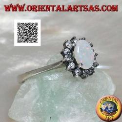 Bague en argent avec petite opale arlequin naturelle ovale entourée de zircons