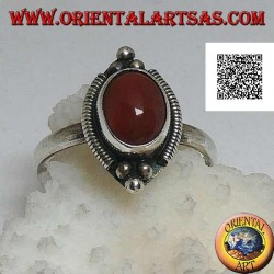 Silver ring with oval cabochon carnelian surrounded by stripes and trio of balls above and below
