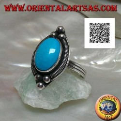 Silver ring with cabochon oval turquoise surrounded by interweaving on a plate and three balls above and below