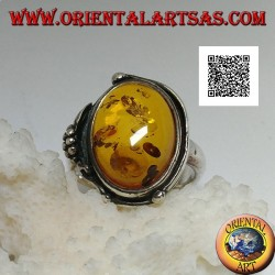 Silver ring with cabochon oval amber with two balls and a leaf on the edge