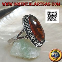 Silver ring with elongated oval amber surrounded by a serpentine in relief