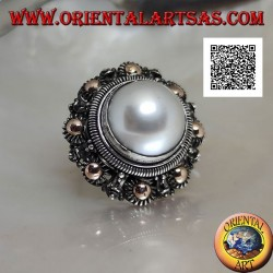 Silver ring with large pearl surrounded by flower decoration and gold plating