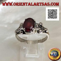 Silver ring with oval garnet set and spiral S between three balls on the sides