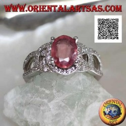 Silver ring with natural oval ruby set between wavy intersecting lines studded with zircons