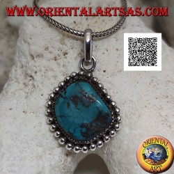 Silver pendant with irregular beveled rhomboidal turquoise surrounded by intertwining and balls