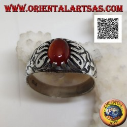 Silver ring with cabochon oval carnelian set with claws and floral decorations in relief on the sides