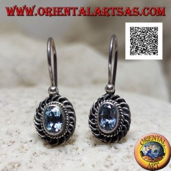 Silver earrings with faceted oval blue topaz surrounded by interweaving and bas-relief quotation marks