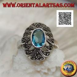 Bague en argent avec topaze bleue ovale sur un ovale convexe perforé parsemé de marcassite