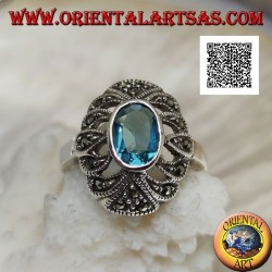 Silver ring with oval blue topaz on an openwork convex oval studded with marcasite