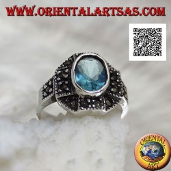 Silver ring with oval blue topaz on cross on octagon studded with marcasite
