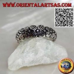Anello in argento a fedina lavorata con fila crescente di fiori a quattro petali in rilievo