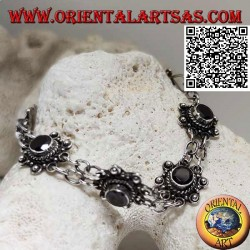 Silver bracelet of 7 flowers with central round faceted garnet joined by two chains