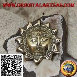 Pendentif népalais en forme de soleil avec un visage en relief en laiton