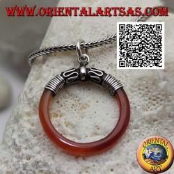 Ciondolo ad anello di corniola infilato in un gancio di argento con decorazione a serpentina