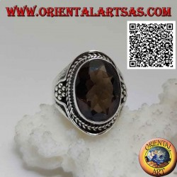 Silver ring with oval faceted smoky topaz surrounded by interweaving and hexagon of balls on the sides