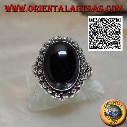 Silver ring with oval cabochon onyx surrounded by a double row of balls and balls on the sides