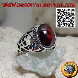Silver ring with oval cabochon garnet on a setting with large floral openwork