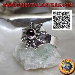 Silver ring in the shape of a pagoda umbrella with a central round garnet