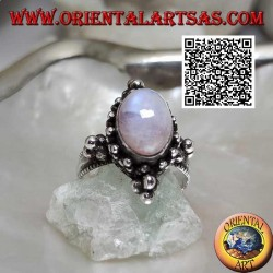 Silver ring with oval cabochon rainbow moonstone on a setting decorated with balls
