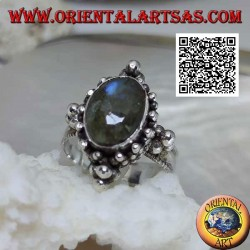 Silver ring with oval cabochon labradorite on a setting decorated with balls