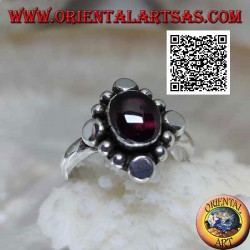 Silver ring with oval cabochon garnet surrounded by alternating studs and balls
