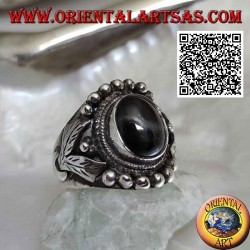 Silver ring with oval black star on ethnic setting with balls and leaves on the sides