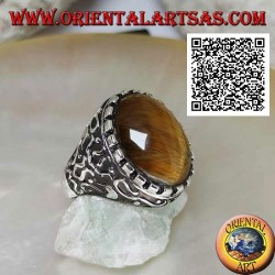Silver ring with large cabochon oval tiger eye surrounded by mystical bas-relief decorations