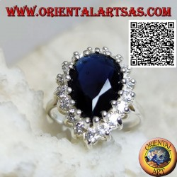 Silver ring with faceted teardrop synthetic sapphire set surrounded by white zircons