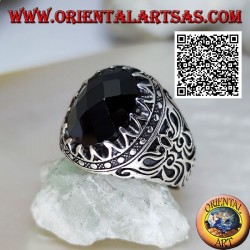 Silver ring with oval cabochon faceted onyx and sinuous designs in bas-relief on the sides